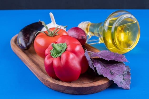 Legumes frescos e garrafa de azeite no prato de madeira