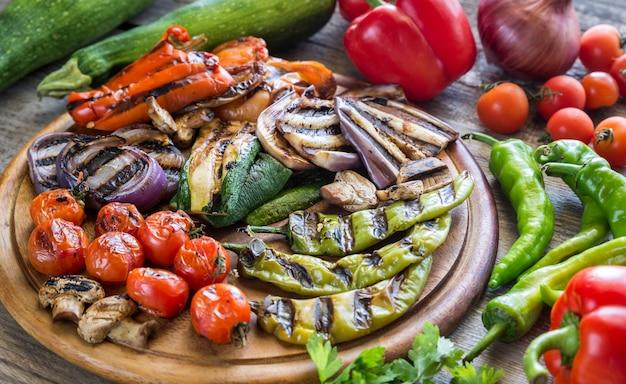 Legumes frescos e grelhados na placa de madeira
