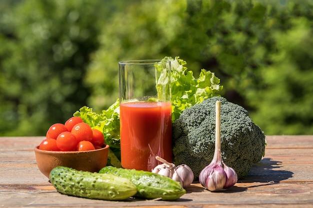 Legumes frescos e suco de tomate na mesa de madeira velha, sobre a natureza verde