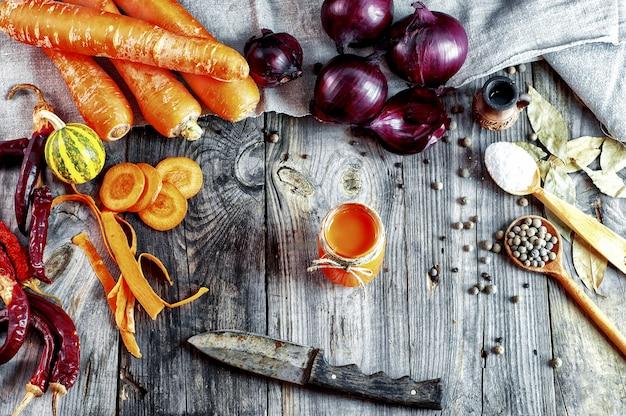 Legumes frescos e um copo de suco de cenoura