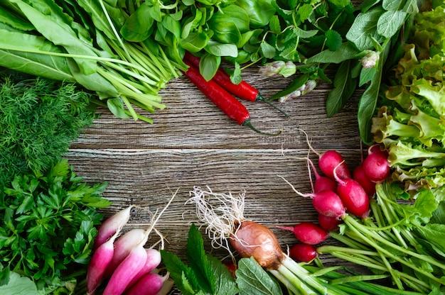 Legumes frescos e verduras. colheita do jardim. produtos úteis em uma mesa de madeira (rabanete vermelho, manjericão, hortelã, sálvia, salsa, cebola, endro, azeda, folhas de alface), espaço livre no meio.