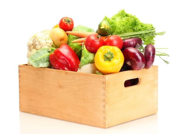 Legumes frescos em caixa de madeira isolados no branco