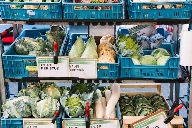 Legumes frescos em caixas azuis na prateleira com etiqueta de preço