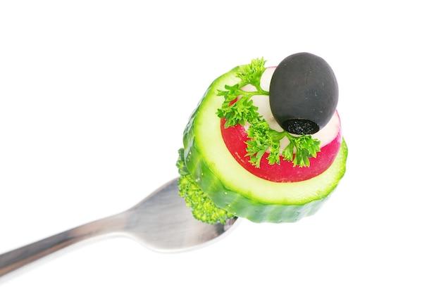 Legumes frescos em um garfo isolado no fundo branco
