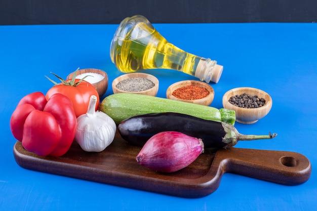 Legumes frescos em um prato de madeira e uma garrafa de azeite com especiarias