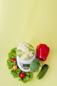 Legumes frescos em um vaso em fundo amarelo. alimentação saudável, planejamento de dieta, perda de peso, desintoxicação, conceito de agricultura orgânica
