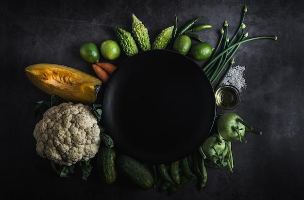 Legumes frescos em uma mesa preta com espaço para uma mensagem