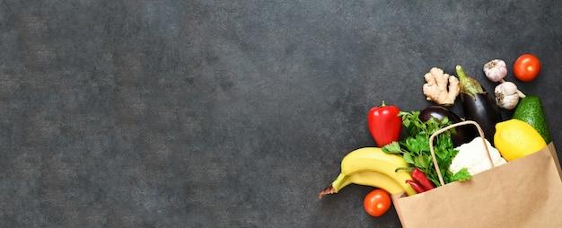 Legumes frescos, frutas e verdes na sacola de papel artesanal em fundo preto rústico. eco compras e conceito de entrega de comida.