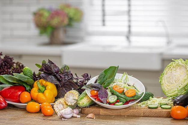 Legumes frescos no processo de preparação de salada em uma mesa de madeira.