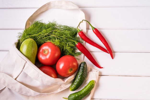 Legumes frescos no saco de compras desperdício zero reusável de matéria têxtil do eco sobre o fundo branco, orientação horizontal.