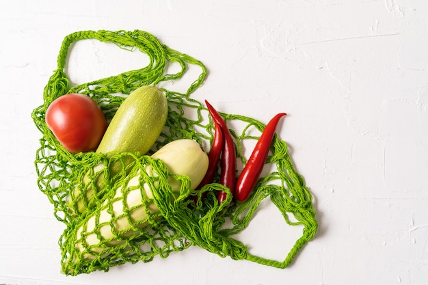 Legumes frescos no saco de compras reusável da malha do desperdício zero do eco sobre o fundo branco, orientação horizontal.