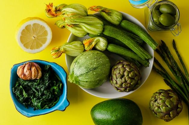 Legumes frescos orgânicos e espinafre cozido em uma tigela sobre fundo amarelo