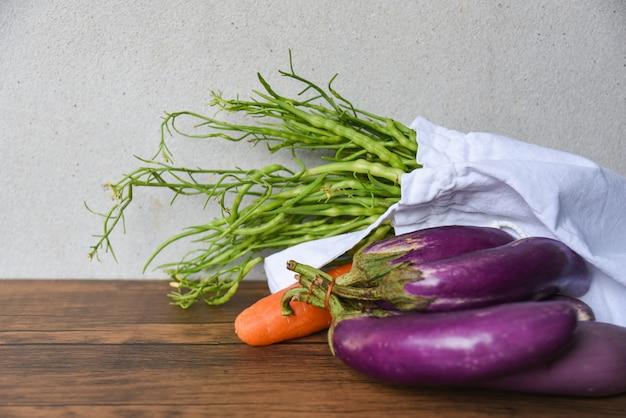 Legumes frescos orgânicos em sacos de tecido de algodão ecológico na mesa de madeira