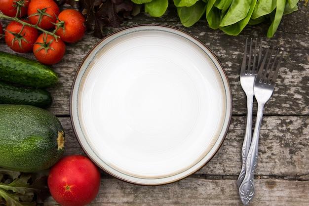 Legumes frescos para vegan saboroso e dieta cozinhar ou salada fazendo em torno do prato vazio no fundo de madeira rústica, vista superior