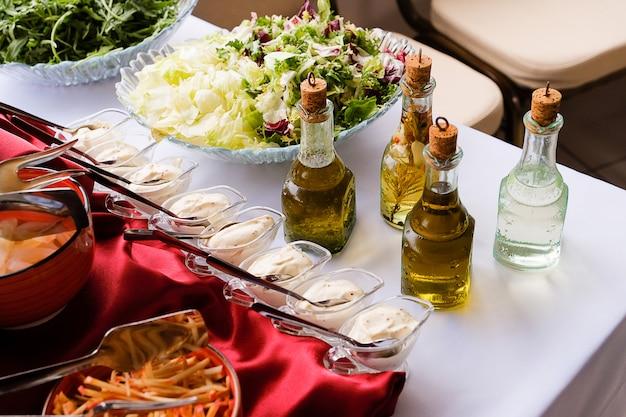 Legumes frescos picados, verduras, molho e molho para salada.