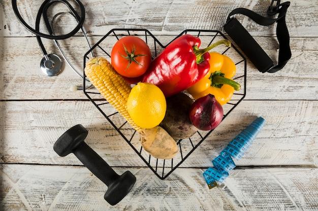 Legumes frescos rodeados por equipamentos de fitness; estetoscópio e fita métrica