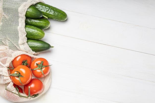 Legumes frescos, tomates e pepinos em sacos ecológicos