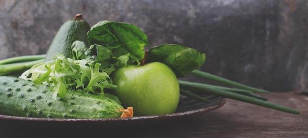Legumes frescos verdes: pepino, alface, cebola, abacate, maçã no fundo antigo