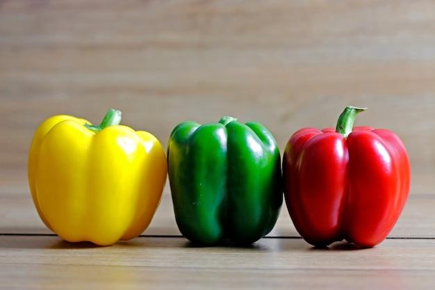 Legumes frescos vermelho, amarelo, verde pimenta na mesa de madeira