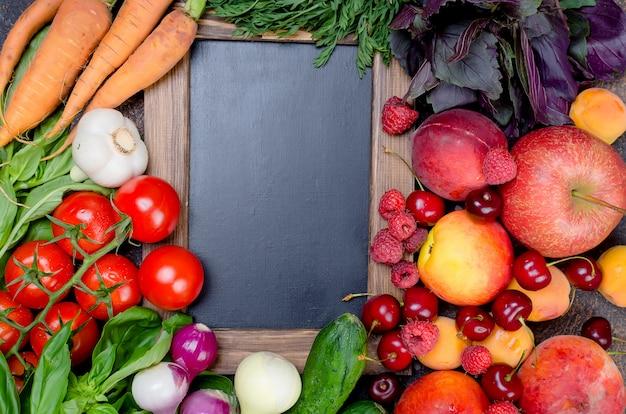 Legumes, frutas e bagas sazonais em torno de um quadro vazio
