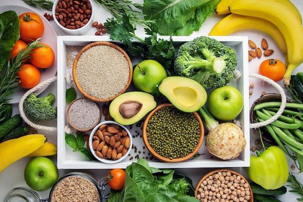 Legumes, frutas e cebolinhas em uma bandeja branca, vista superior. conceito de comida vegana.