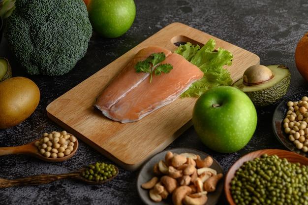 Legumes, frutas e pedaços de peixe salmão em uma tábua de madeira.