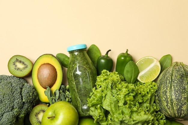 Legumes, frutas e smoothie em fundo bege
