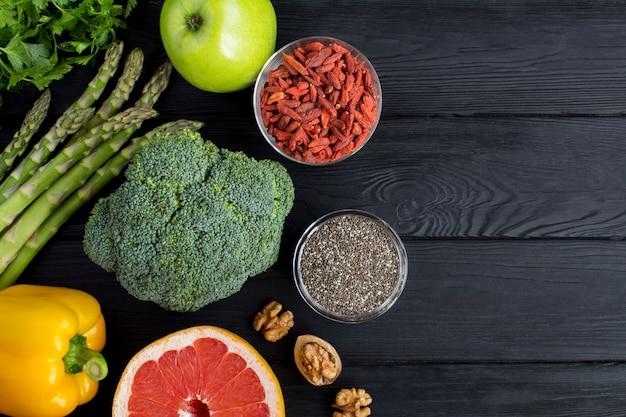 Legumes, frutas, sementes de chia e bagas de goji na superfície de madeira preta.