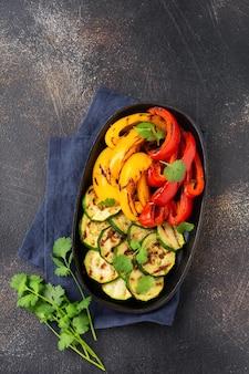 Legumes grelhados abobrinha, pimentão vermelho e amarelo, pimentão e buquê de coentro na assadeira. vista do topo. conceito de churrasco.