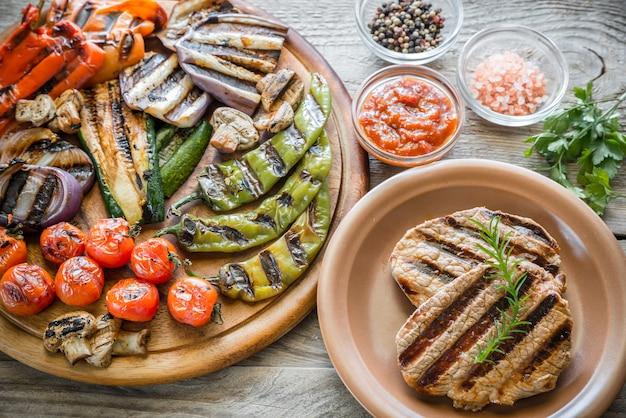 Legumes grelhados com bife na placa de madeira