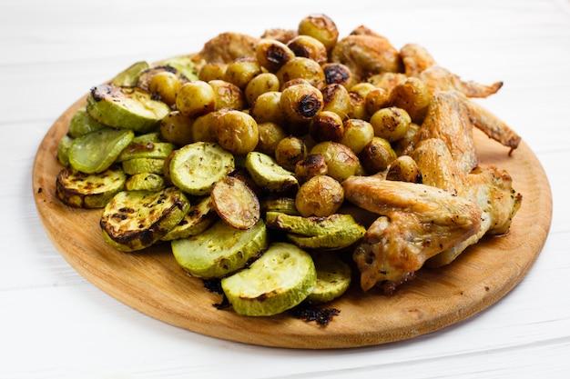 Legumes grelhados e asas de frango na chapa de madeira