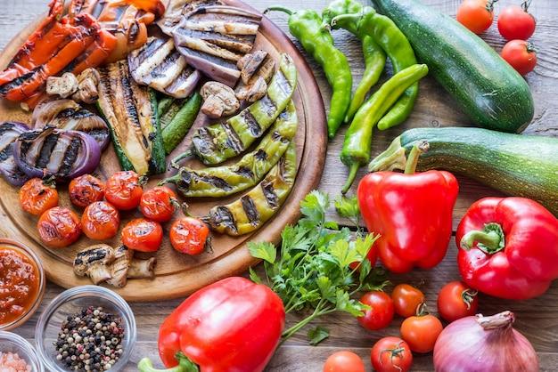 Legumes grelhados e frescos na placa de madeira
