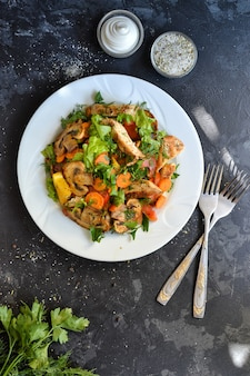 Legumes grelhados e salada de peito de frango. peito de frango, salada, cogumelos, tomate, laranja.