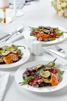 Legumes grelhados em pratos brancos. prato de restaurante