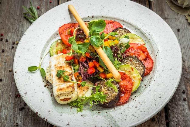Legumes grelhados, queijo suluguni grelhado, em uma mesa de madeira