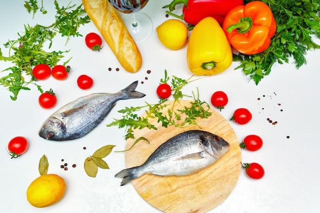 Legumes maduros e peixe na mesa da cozinha