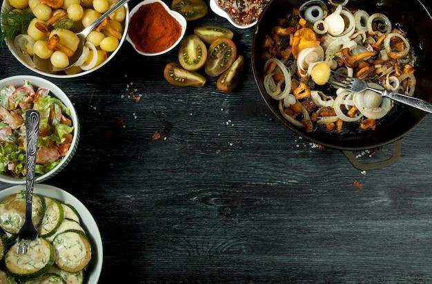 Legumes . molho de abobrinha frito em um prato. jovens batatas cozidas com endro em uma tigela. cogumelos chanterelle fritos com cebolas douradas em uma frigideira. copyspace
