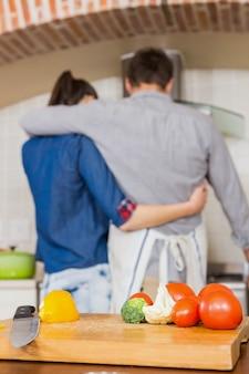 Legumes na tábua e casal abraçando enquanto prepara uma refeição na cozinha
