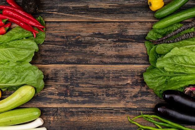 Legumes nos lados direito e esquerdo do quadro em uma mesa de madeira