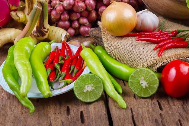 Legumes orgânicos crus variados na velha mesa de madeira