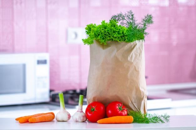 Legumes orgânicos em saco de papel na mesa para cozinhar pratos de vegetais e saladas na cozinha. comida saudável, dieta equilibrada. comer limpo