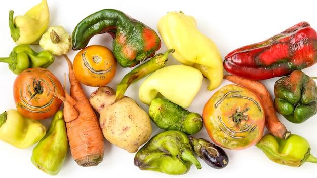Legumes orgânicos feios da moda: batata, cenoura, pepino, pimentão, pimentão, berinjela e tomate no fundo branco, conceito de comida feia, orientação horizontal