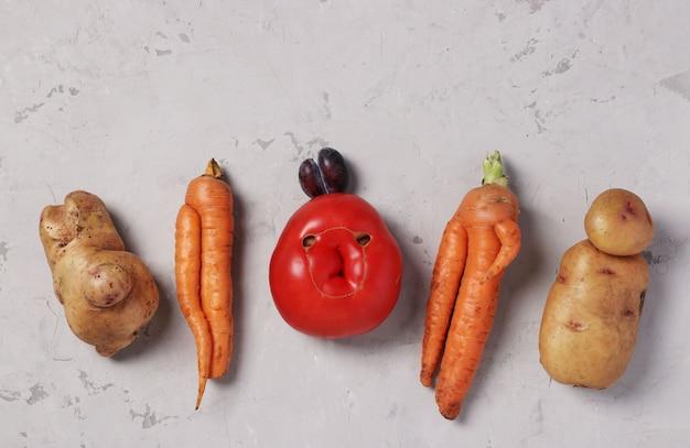 Legumes orgânicos feios da moda: batatas, cenouras, tomate e ameixa na mesa cinza, conceito de comida feia, formato horizontal, vista de cima