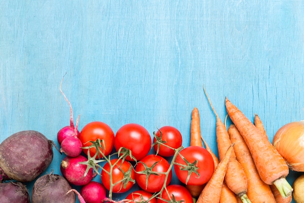 Legumes orgânicos frescos, cuidados de saúde, sobre um fundo azul de madeira. colheita. estilo sertanejo. conceito de uma feira agrícola. vista plana, vista superior