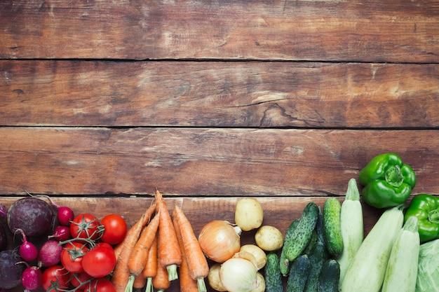 Legumes orgânicos frescos, cuidados de saúde, sobre um fundo de madeira. colheita. estilo sertanejo. conceito de uma feira agrícola. vista plana leiga, superior. copie o espaço