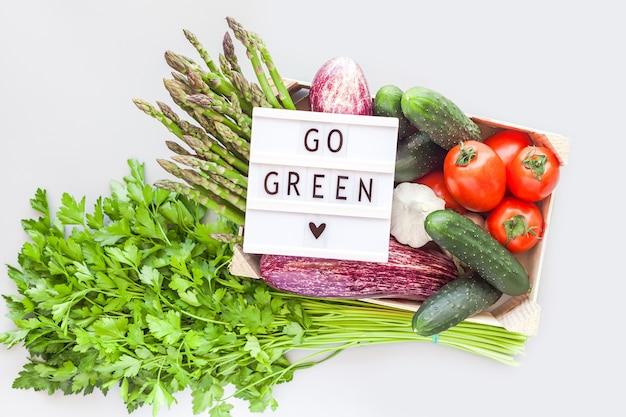 Legumes orgânicos frescos em caixa de madeira ecológica com o texto go green lightbox