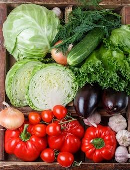 Legumes orgânicos frescos em caixa de madeira - repolho, tomate, pimentão, berinjela,