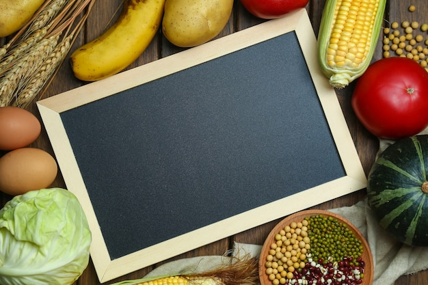 Legumes orgânicos frescos, frutas, ovos, feijões e grãos com quadro-negro na mesa de madeira vintage