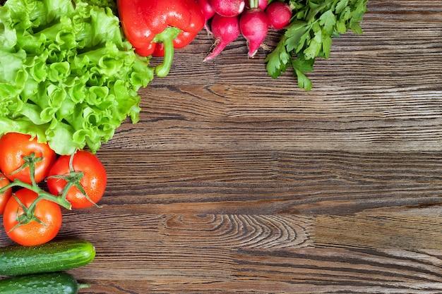 Legumes orgânicos frescos na mesa de madeira marrom. vista de cima, configuração plana.