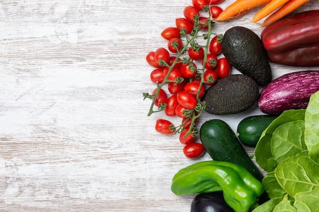 Legumes orgânicos frescos no fundo de madeira branco. alimento natural saudável na tabela com espaço da cópia.
